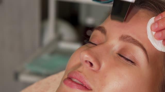 young woman undergoing ultrasonic facial treatment at beauty salon - kosmetyczka praca w salonie piękności filmów i materiałów b-roll