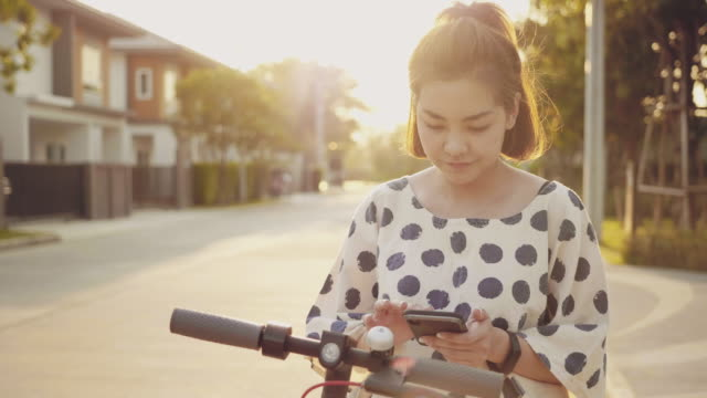 young woman unlocking electric push scooter with cellphone - monopattino elettrico video stock e b–roll