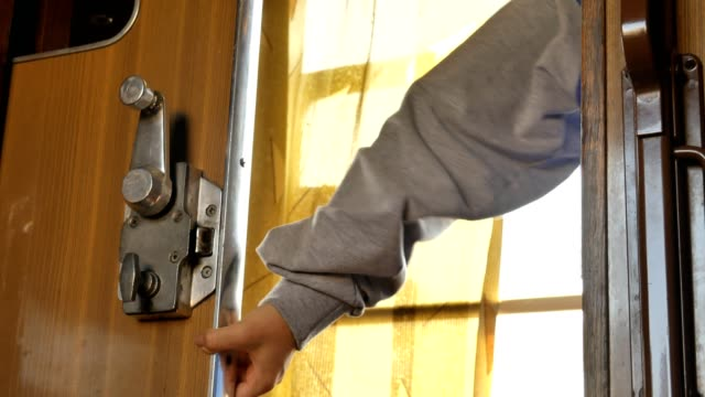 A young woman unlocks and opens a door with metal handle and exits train compartment. A train passenger unlocks door from inside and opens it.