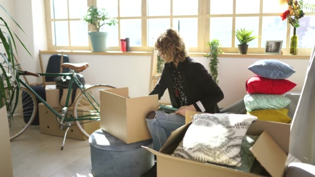 Young woman unpacking boxes at new apartment