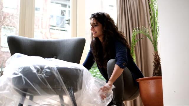 vídeos de stock e filmes b-roll de jovem mulher unwrapping cadeira novo - new