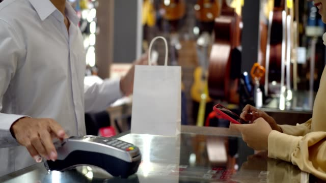 young woman use smartphone paying over contactless transaction machine - struttura pubblica video stock e b–roll