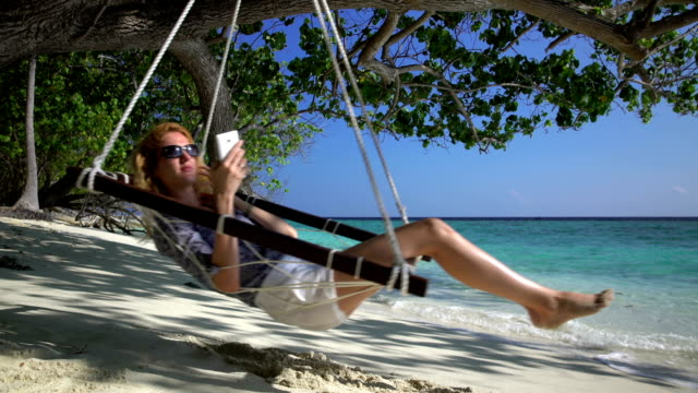A young woman uses a smartphone and enjoys relaxing on the tropical beach in a hammock. video