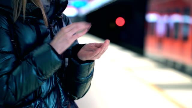 vídeos y material grabado en eventos de stock de una joven usa líquido desinfectante de manos en una estación de metro - hand sanitizer