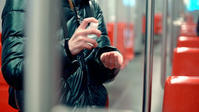 A young woman uses hand sanitizer liquid in a subway car A young woman uses hand sanitizer liquid in a subway car, pandemic coronavirus concept travel stock videos & royalty-free footage