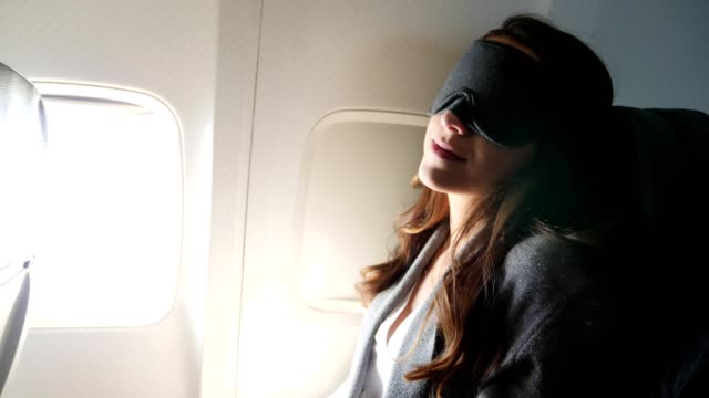 young woman uses sleeping mask during a long flight - sedili aereo video stock e b–roll