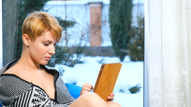 Young woman uses tablet sitting near the window video