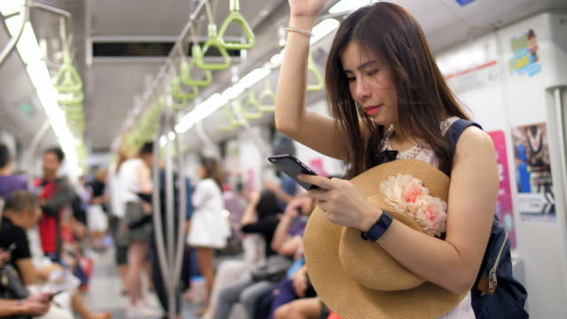 Young woman uses the smartphone in public transportation