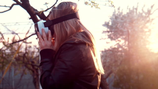 Young woman uses VR helmet with pleasure video