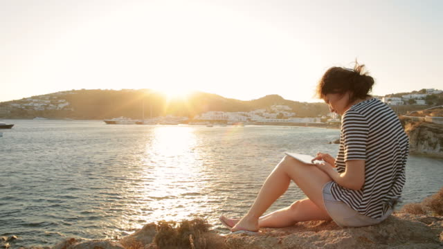 Young woman using a digital tablet while relaxing on the shore. video
