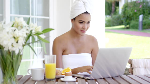 Young woman using a laptop while having breakfast Young woman wrapped in a clean fresh white towel sitting on an outdoor patio using a laptop while having breakfast wearing a towel stock videos & royalty-free footage