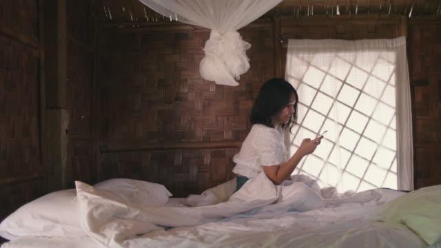 junge frau mit einem smartphone beim sitzen im weißen bett im schlafzimmer genießen wind in ihrem haar. - moskitonetz stock-videos und b-roll-filmmaterial