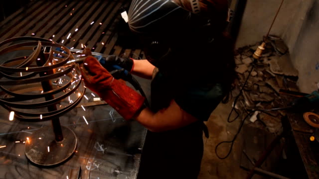 Young woman using a welding machine There are two woman and one man, they are in their shop, working together. welder stock videos & royalty-free footage