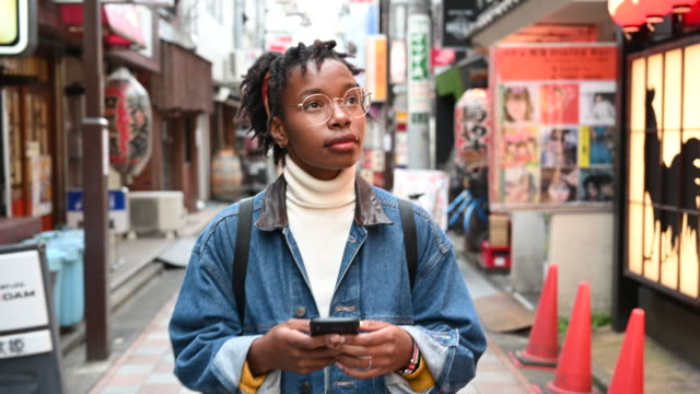 young woman using app exploring streets of tokyo - esploratore video stock e b–roll