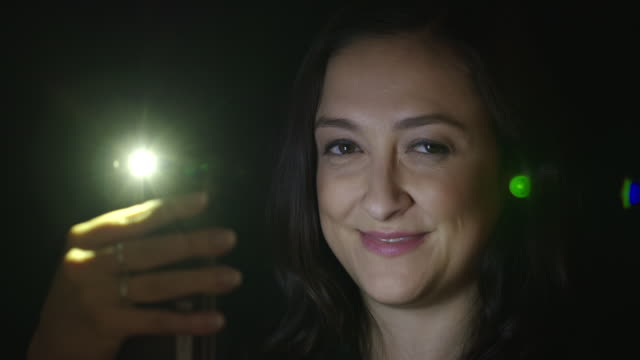 Young woman using cellphone at night smiles to camera 4K video