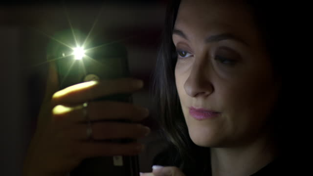 Young woman using cellphone at night turns to camera 4K video