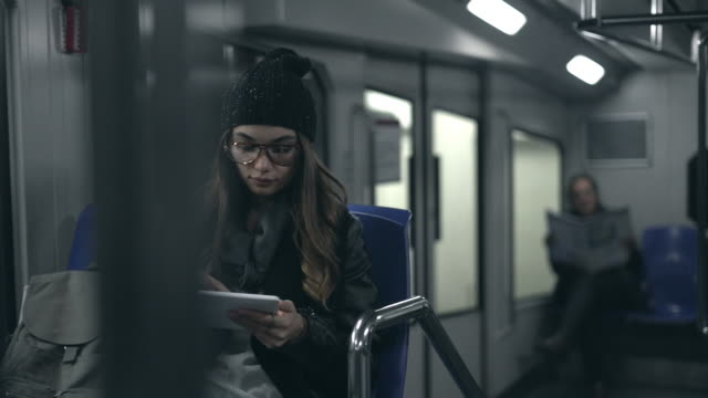 Young woman using digital tablet in metro Young woman using digital tablet in metro subway train stock videos & royalty-free footage