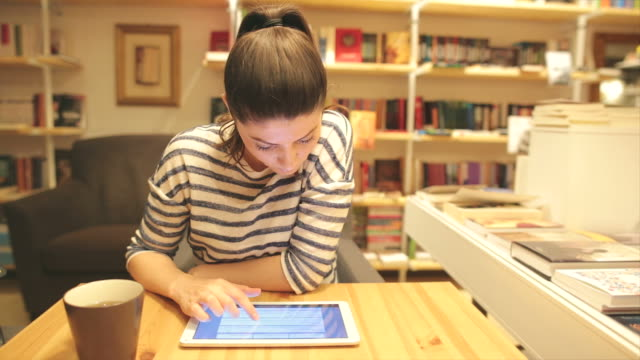 Young woman using digital tablet in the bookstore. video