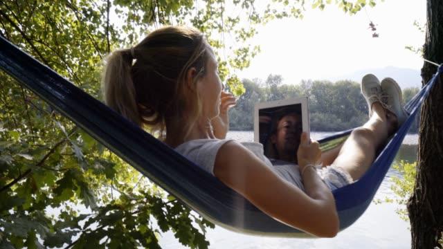 在吊床上使用數位平板電腦的年輕婦女 - 休閒器具 個影片檔及 b 捲影像