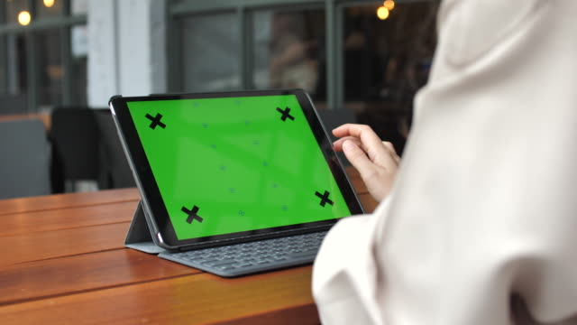 Young woman using digital tablet with a green screen