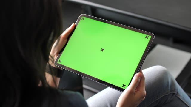young woman using digital tablet with green screen on sofa, horizontal - ipad video stock e b–roll
