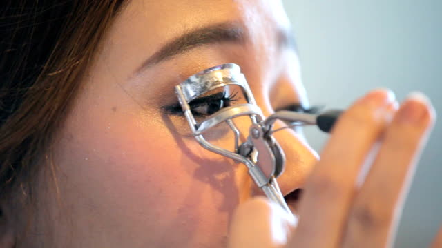 Young woman using eyelash curler video