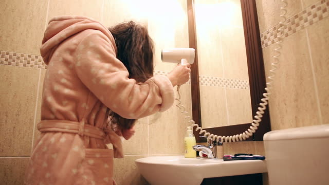 Young woman using hairdryer. video