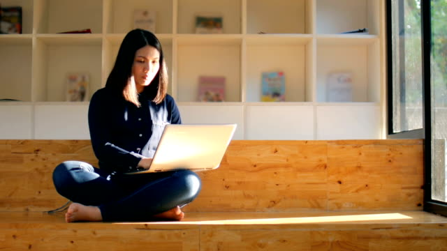 Young woman using her laptop in library , working at home footage concept Young woman using her laptop in library , working at home footage concept wide angle stock videos & royalty-free footage