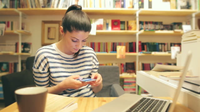 Young woman using her smart phone in the library. video