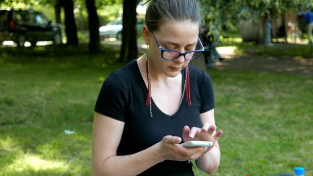 молодая женщина, используя ее смартфон в парке - google стоковые видео и кадры b-roll