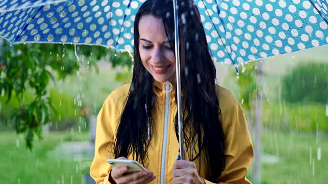 SLO MO Young woman using her smartphone in the rain