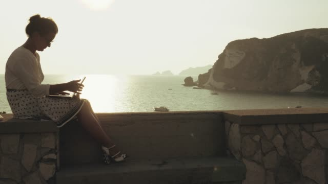young woman using laptop at the beach opening and closing the lid, at sunset on ponza island, italy. fashion white shirt and skirt. - coperchio video stock e b–roll