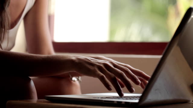Young woman using laptop computer at home video