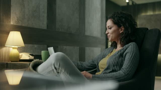 giovane donna utilizzando un computer portatile sul divano - comodità video stock e b–roll