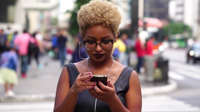 junge frau mit handy - mobile app stock-videos und b-roll-filmmaterial