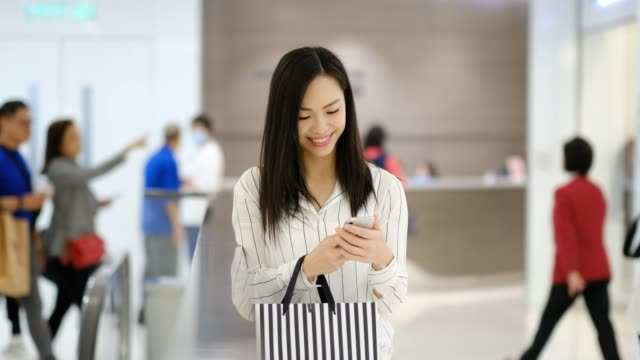 Young Woman using of mobile phone in shopping mall