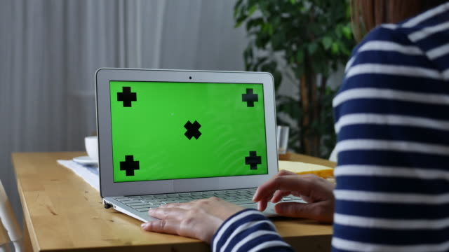 Young woman using on computer laptop with green screen,Dolly shot video