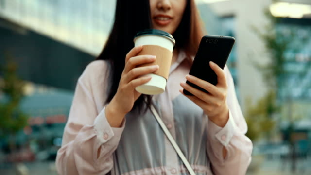 young woman using phone and drinking coffee - bevanda calda video stock e b–roll