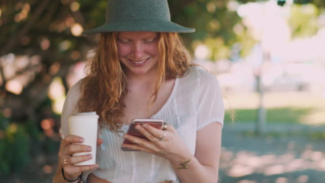 Young woman using phone in a park Young woman standing in the park. She is using phone and smiling. Green trees in the back. redhead stock videos & royalty-free footage