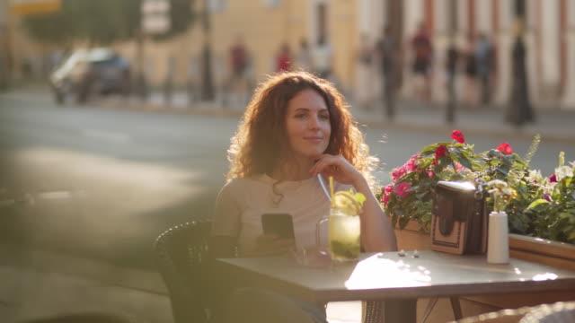 屋外カフェで電話を使う若い女性 - パティオ点の映像素材/bロール