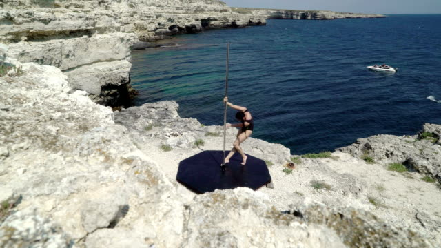 Young woman using portable free standing dance and fitness pole Young woman using portable free standing dance and fitness pole during outdoor workout on a rock above the sea leotard stock videos & royalty-free footage