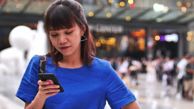 若い女性の群衆の中の人にスマート フォンを使用して - 通販点の映像素材/bロール