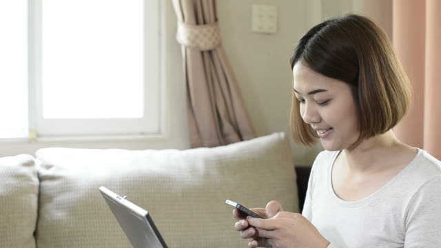 Young woman using smartphone at home video