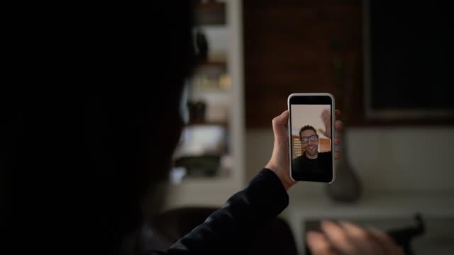 junge frau mit smartphone für videoanruf - anruft ihren freund - smartphone mit corona app stock-videos und b-roll-filmmaterial