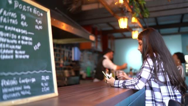 młoda kobieta za pomocą smartfona w barze licznik - surfować po internecie filmów i materiałów b-roll