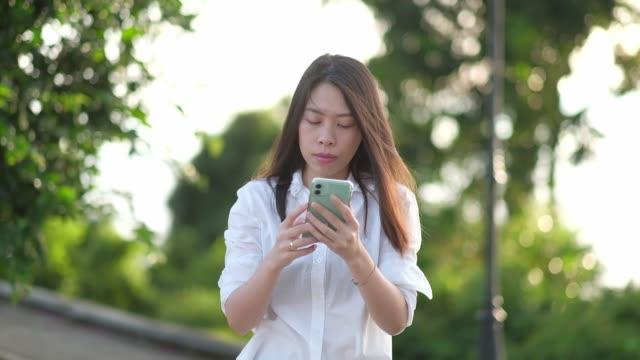 vídeos de stock e filmes b-roll de young woman using smartphone in beautiful morning sunrise. - só mulheres jovens