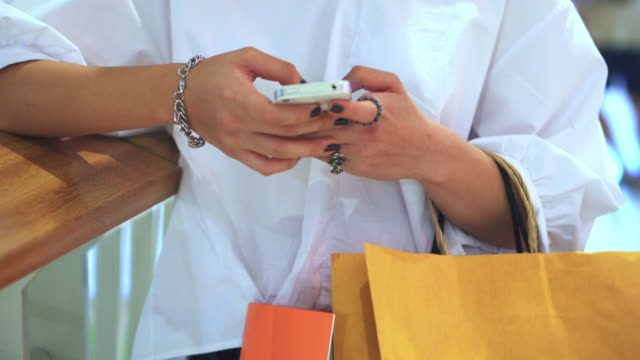 Young woman using smartphone  in shopping mall video