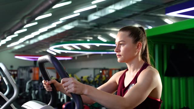 young woman using stair stepper while having cardio workout in gym - sprzęt do ćwiczeń filmów i materiałów b-roll