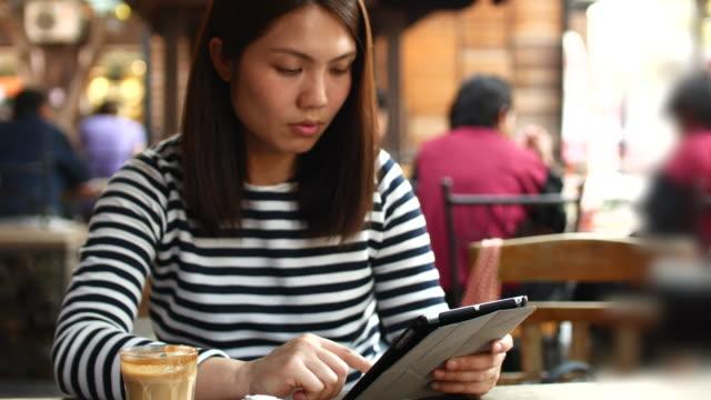 Jeune femme à l'aide de Tablette PC et boire du café au Café, 4 k (UHD - Vidéo
