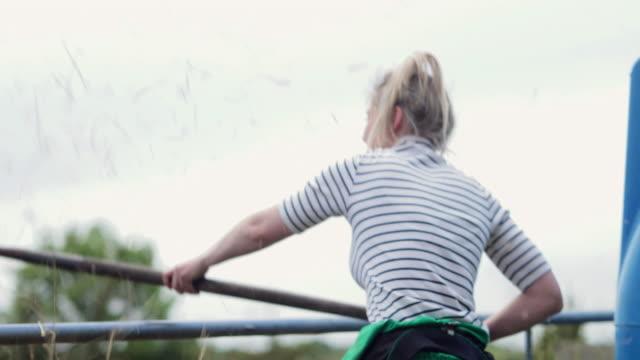 vídeos de stock e filmes b-roll de young woman using the hay fork - agricultora
